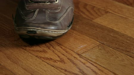 deslizamento : A foot slips on water dripping from above on a wood floor
