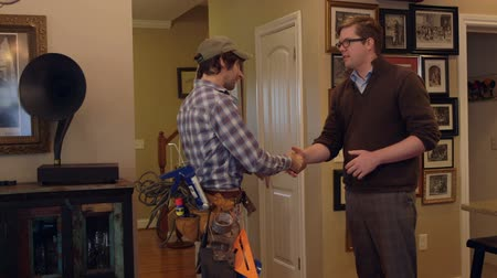 müteahhit : A contractor and home owner shake hands inside a house as they agree on a project