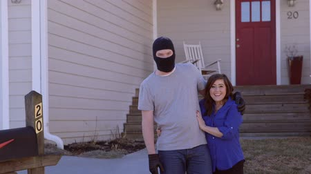 ladrão : A thief wearing a ski masks stands in front of a contemporary, modern, house with his arm around a woman Vídeos