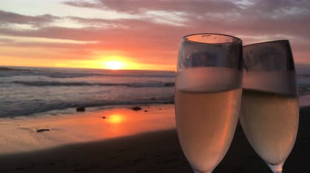 esküvő : Two glasses of champagne clink and then pull away against a magnificent sunset on the beach