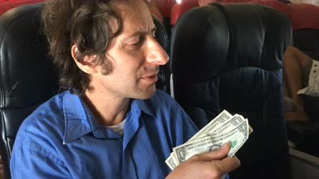 trener : A weary traveler tries to buy something with cash on an airplane Wideo