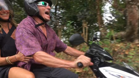gritar : Two people riding a scooter appear to be out of control in the jungle on a very narrow road.