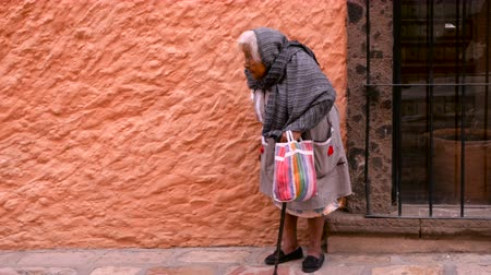 cidadão idoso : SAN MIGUEL DE ALLENDE, MEXICO - CIRCA MAY 2016 - An old indigenous woman walks with a cane in a historic town.