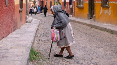головной убор : SAN MIGUEL DE ALLENDE, MEXICO - CIRCA MAY 2016 - An old indigenous woman crosses the street in San Miguel de Allende, Mexico