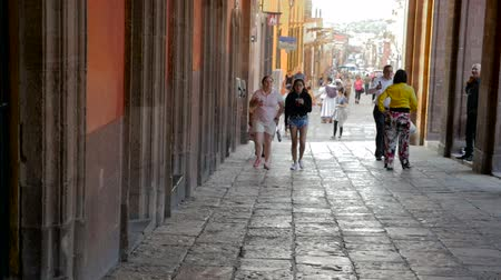 pedestrian only : SAN MIGUEL DE ALLENDE, MEXICO - CIRCA MAY 2016 - Tourists walk in the streets closed to traffic while enjoying drinks in slow motion