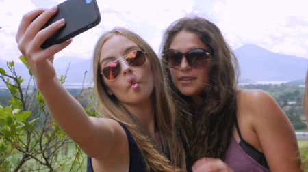 melhor : Young beautiful teenage girls make silly faces for a selfie in slow mo in the summer overlooking a mountain view