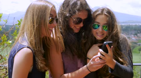 selfie girl : Three lovely teenage girls with beautiful long hair look at their smart phone together, smile, and laugh, in slowmo while standing on a terrace overlooking mountains and a green landscape.