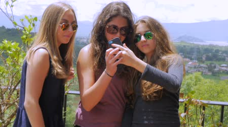 selfie girl : Three gorgeous teenage girls take multiple selfies and look at their cell phone in slow mo while standing outside on a sunny day with mountains and green landscape in the background. Stock Footage