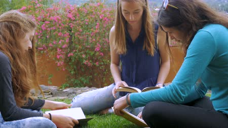 gramado : Three young woman read books outside together while sitting on the green grass in slow motion Stock Footage