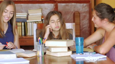 aluna : Three beautiful teenage girls learn together with books at a table in a modern looking home with dolly shot.