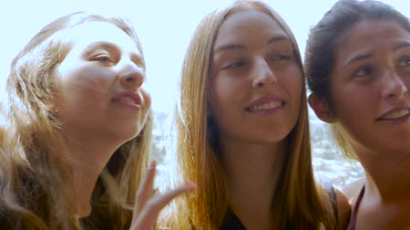 melhor : Three teenage girls take a selfie outside and share it with each other on their smart phone while having a good time. Vídeos