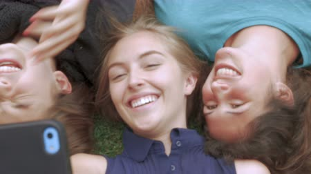 selfie girl : Attractive teenage girls having fun with their cellphone taking selfies in the grass Stock Footage