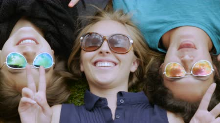 nastolatki : Three teenage girls lying in the grass making silly faces to the camera while wearing sunglasses
