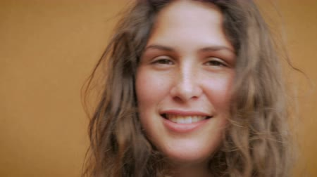 ona : Close up portrait of a young attractive woman with long brown hair and freckles smiling for the camera as she takes off her sunglasses Dostupné videozáznamy