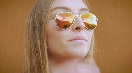 suçsuzluk : An attractive blond teenage girl smiles and takes off her sunglasses - hand held