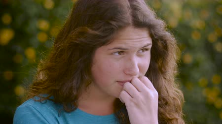 apprehensive : A nervous distressed attractive young woman looks off in the distance with her hand on her chin Stock Footage