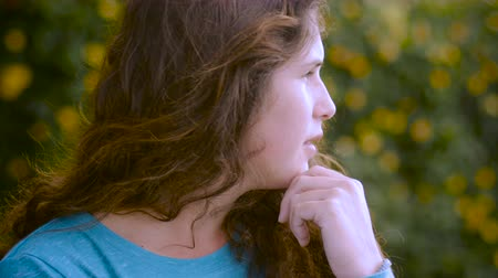 apprehensive : A young woman with long brown hair looks off in the distance thinking with her hand on her chin Stock Footage