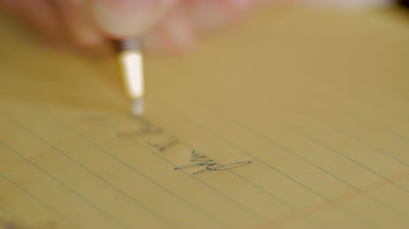 подпись : Closeup of person signing name with ballpoint pen on yellow notebook by hand Стоковые видеозаписи