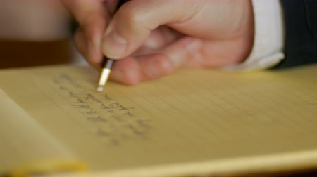 yazarak : Businessman hand writing letter in legal pad yellow notebook with ball point pen CLOSE UP Stok Video