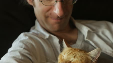 abraços : A man gently pets his orange cat while holding it in his arms in slow motion