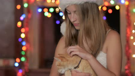 memeli : A smiling young attractive woman wearing a Santa hat petting an orange tabby cat in her lap with colored Christmas lights in the background - dolly shot