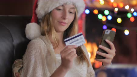 értékesítés : A happy attractive young female shopper wearing a Santa hat finishes her online purchase on her smart phone during the holidays with Christmas lights in the background - push in
