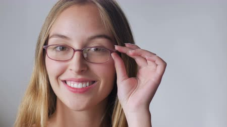 szemüveg : An attractive young woman with long blond hair tries on eyeglasses and smiles against a white background