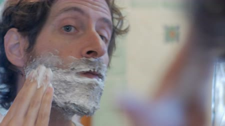 barbear : Close up of an attractive man putting on shaving cream on a full beard - handheld