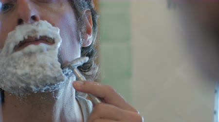 tuvalet : An attractive man uses a single blade safety razor to shave his beard - handheld
