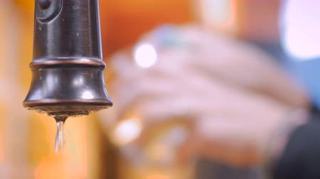 hydraulik : Extreme close up of a leaking faucet with a person washing dishes in the background Wideo