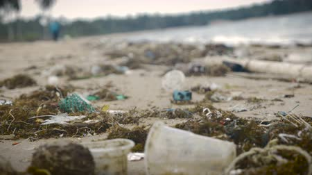 plastic cups : Plastic trash and waste litter an empty beach - handheld tilt up Stock Footage