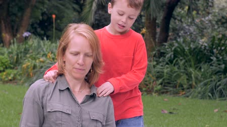 com medo : A nervous mother is concerned and distracted by something while her son massages her shoulders - slowmo Vídeos