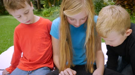 conectado : 3 young cute kids or siblings, two blond haired and one red head boy play on a tablet outside - slowmo crane shoot