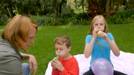 único : A redheaded mom comes to help her youngest son blow up balloons - slowmo steadicam