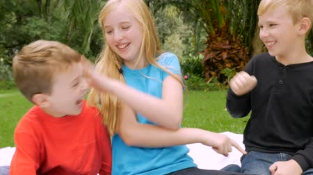 annoying : Three young siblings poking and tickling each other outside in a park or garden - slowmo handheld
