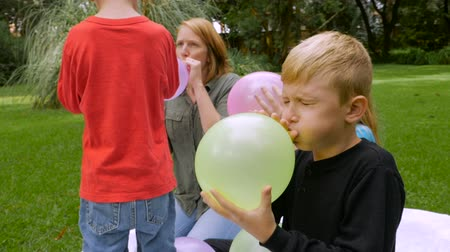 obtížný : A redheaded mother and her 2 sons and daughter blow up balloons together outside all working towards a common goal - slowmo