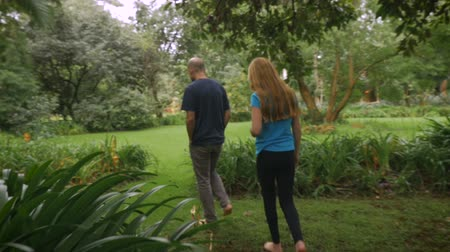 łysy : The camera follows a father and daughter walking barefoot through a park - slowmo steadicam