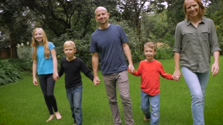 suçsuzluk : A smiling happy family of 5 look at and walk towards the camera - slowmo steadicam