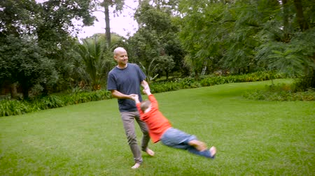 suçsuzluk : A father spins his 5 year old son around in circles on the grass - slowmo steadicam Stok Video