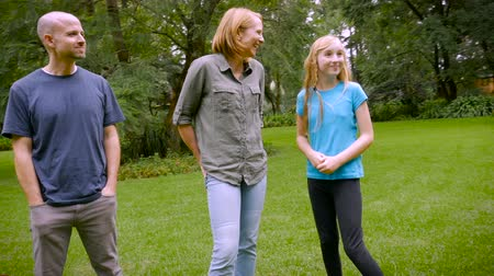 walking man : A family of 5 standing around in the grass barefoot - slowmo steadicam