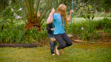 país : A little blond haired boy pushes a young girl on a swing in a park - slowmo.
