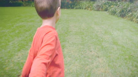 yards : A young boy leading and pulling someone while running through the grass - slowmo. It appears that he is pulling his mom or dad towards something he is excited about.