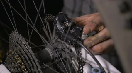 pneus : Close up of a bike mechanics hands making minor adjustments to the disc brakes of a mountain bike on a garage or repair shop.