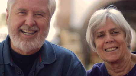 yaşlanma : An attractive elderly couple with gray hair smiling and laughing outside. The baby boomer man has a gray beard and the senior woman has short hair both wearing blue.
