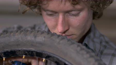 csavarkulcs : A handsome millennial man works on a mountain bike with an allen wrench and tire