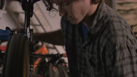 zmiany : Pan up of a young attractive bike mechanic working on a mountain bicycle while spinning the rear wheel
