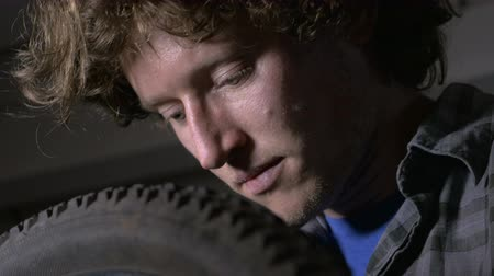opravář : Closeup portrait of a handsome millennial man looking down at a bike tire while working on a bicycle Dostupné videozáznamy