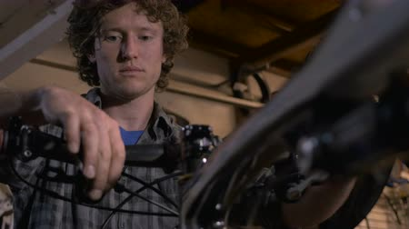 csavarkulcs : A bike mechanic fixes the front end of a bicycle - low angle