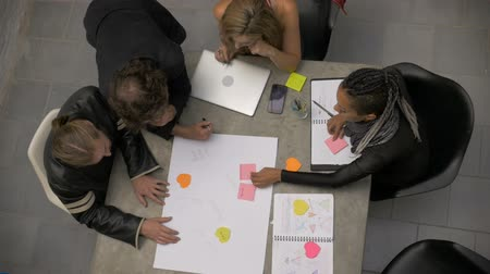 havai : Overhead of a mixed race group of millennials collaborating and brainstorming together in slow motion writing on a large piece of paper with colored note pads. Stok Video