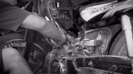 szerelő : Black and white dolly shot of a mechanic cleaning and draining gasoline from a partially disassembled motorcycle in Bali, Indonesia utilizing simple tools in a basic workshop Stock mozgókép